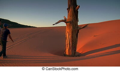 two people walk up red sand dune at sunset