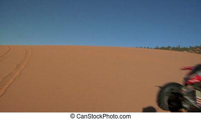 slow-motion ATV riders on sand dunes