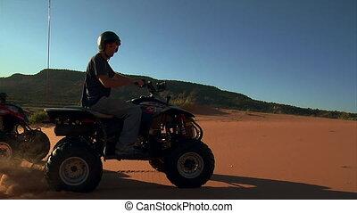 high shutter speed  ATV riders race on sand dunes