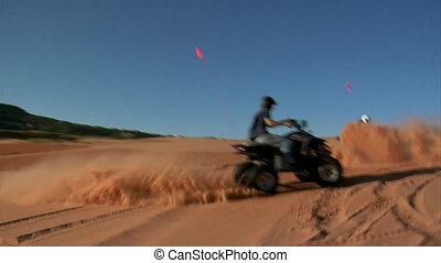 slow-motion ATV riders kick up sand