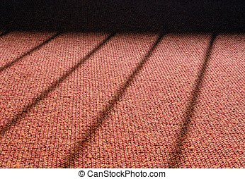 Shadow of a window grille on a carpet