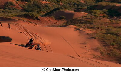 ATV riders on red sand dunes