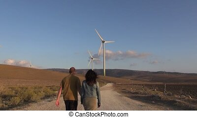 couple walking to wind energy - wind power mills next to...