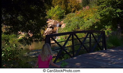 mother and children cross the bridge and admire pond and waterfall