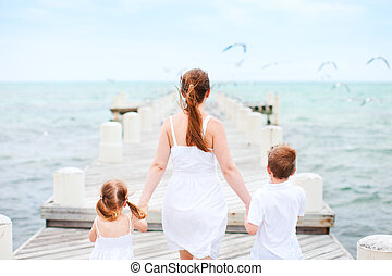 Mother and kids at seaside - Back view of mother and kids on...
