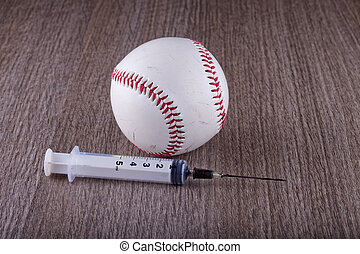 Baseball and syringe - A baseball near a syringe over wooden...