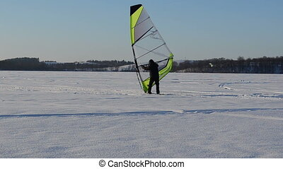 winter sport leisure - man ice sailing surfing on frozen...