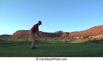 steadicam shot of man teeing off on golf course with sunset and red rock cliffs