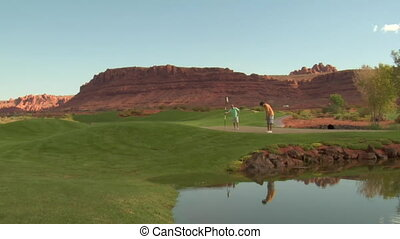 father and son putt on golf course with pond and red rock cliffs