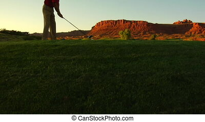 jib shot of man teeing off on golf course with sunset and...