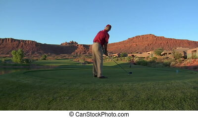 steadicam shot of man teeing off on golf course with sunset...