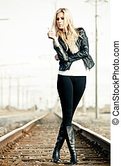 On a railroad - Young woman standing on a railroad and...