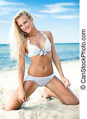 On a beach - Sexy blond girl posing on a beach