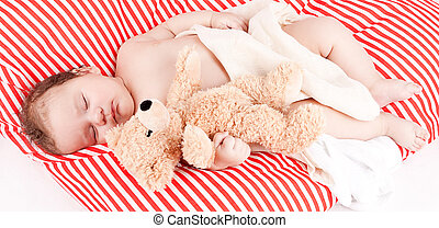 sleeping cute little baby on red and white stripes pillow...
