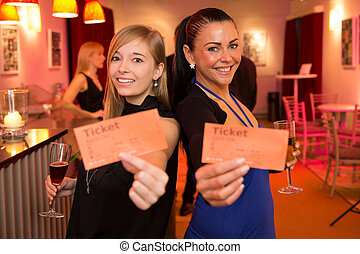 Two women presenting theatre or movie tickets