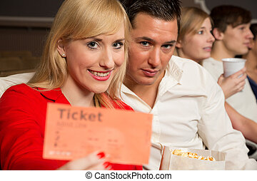 Audience member presenting tickets - People in a theatre, a...