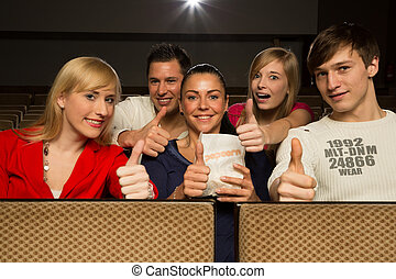 People in a movie theatre having fun and showing thumbs up