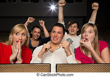 Audience in cinema cheering - Audience in movie theatre...