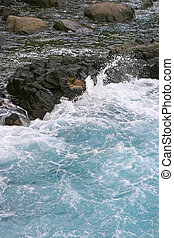 Cyan turbulent water - The swirlign water crashes on the...