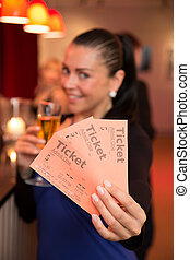 Woman in theatre presenting tickets - A beautiful woman in a...