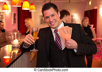 Man in a theatre or cinema presenting tickets