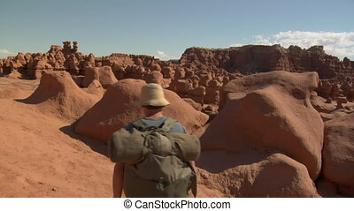 jib shot as man climbs over rocks in goblin Valley Utah
