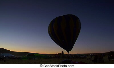 silhouette of a hot air balloon being filled in the early...
