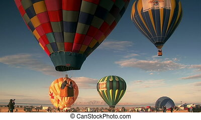 multiple hot-air balloons ascend into the sky