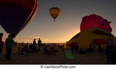 spectators watching hot-air balloons being filled and...