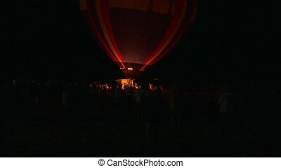 hot air balloons are filled in the pre-morning darkness