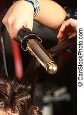 Working Hairstylist Curling Hair in a Salon - Hairstylist...