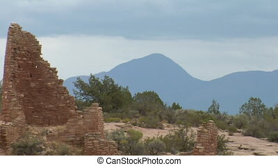 zoom out shot of mountains revealing ruins  at Hovenweep national Monument