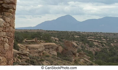 zoom out shot of mountains revealing ruins at Hovenweep...