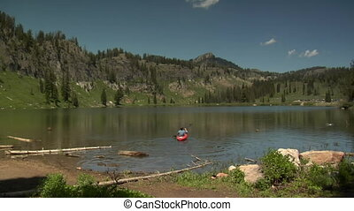 man kayaks on calm Mountain Lake