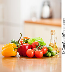 Healthy food fresh vegetables  and bottle with oil on the kitchen table