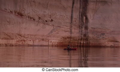man kayaks red rock canyons on Lake Powell the