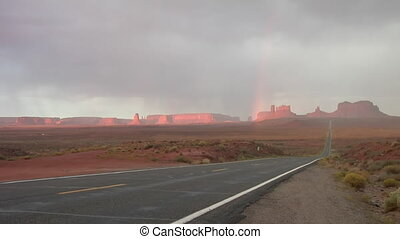 Monument Valley highway with rainbow wide shot