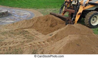 Front End Loader Moves Dirt Pile - A front end loader moves...