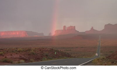 Monument Valley highway with rainbow