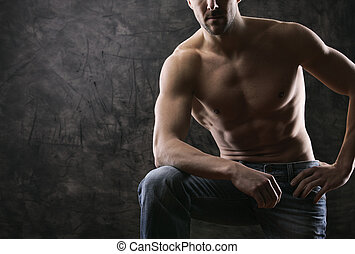 trained body wearing demim - Sexy muscular man on dark...