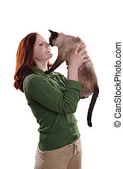 happy young woman rubbing nose with siamese cat