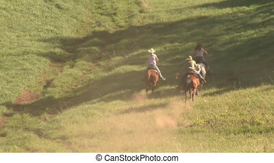 three young women on horses gallop across green meadow–with...