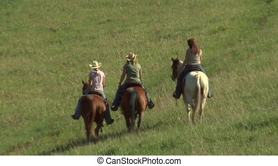 three young women on horses ride across green meadow- zoom...