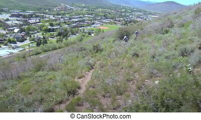 Two mountain bikers head downhill on dusty trail