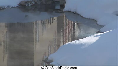 steaming water with snowbank