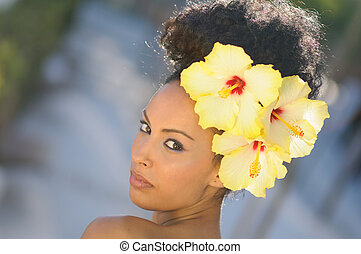 Black woman, model of fashion, with big flowers in her hair