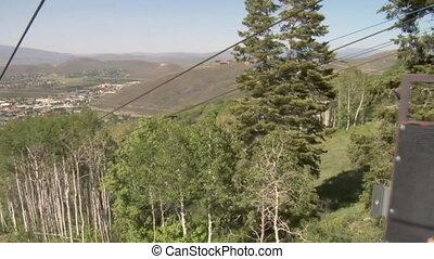 Two girls go down a mountain zipline