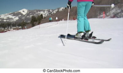 A teen girl skiies downhill in slow motion