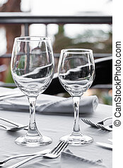 Two wine glasses empty on a table.