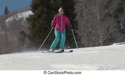 Teen girl zips past on skiies on groomed hill
